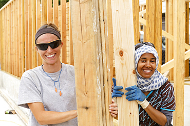 Smiling volunteers holding lumber at construction site