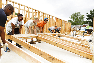 Volunteers lifting framed wall at construction site