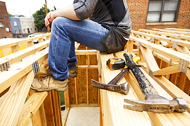 Caucasian man resting near hammer and tape measure