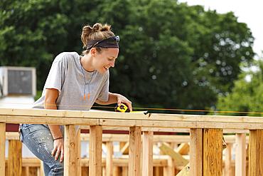 Caucasian woman measuring at construction site