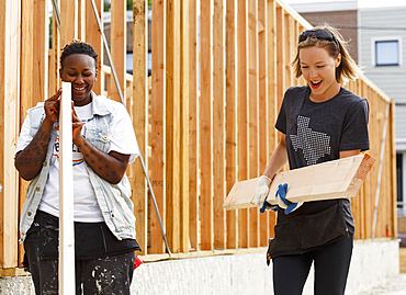 Volunteers carrying lumber at a construction site