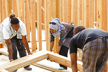 Volunteers lifting wooden frame at construction site