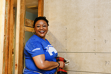 Portrait of smiling black woman holding drill