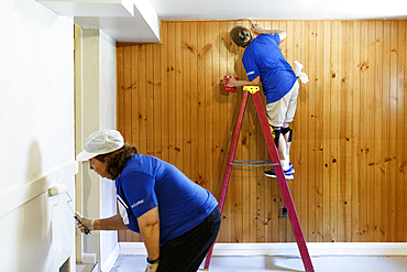 Women painting wall and ceiling