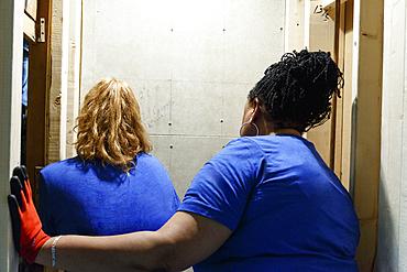 Women examining wall