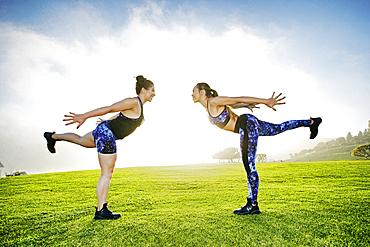 Mixed race women standing on one leg in field