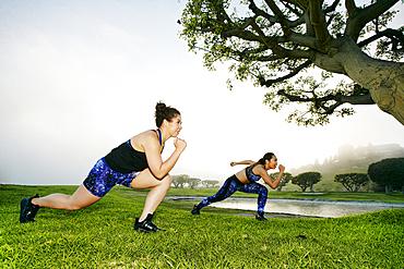 Mixed race women exercising near lake
