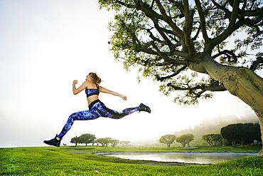Mixed race woman running near lake