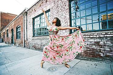 Mixed race ballet dancer wearing dress on sidewalk