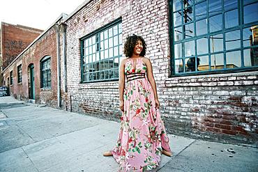 Smiling mixed race ballet dancer wearing dress on sidewalk