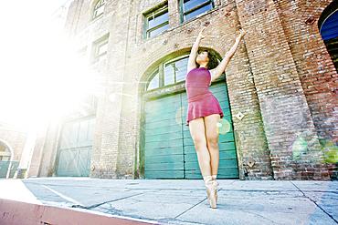 Sunbeams on mixed race woman dancing in city