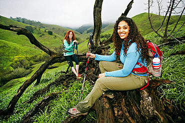 Smiling hiking women resting on a tree