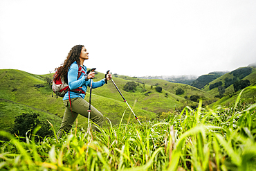 Smiling mixed race woman hiking with walking sticks