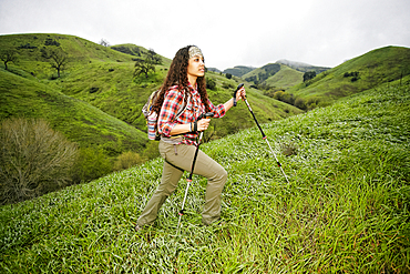 Mixed race woman hiking with walking sticks
