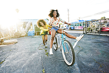 Friend pushing carefree woman on bicycle