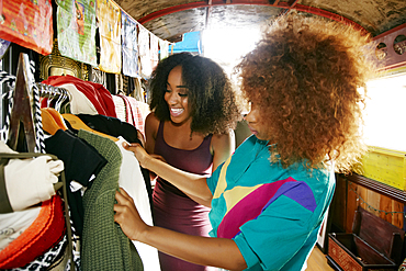 Women examining clothing in retail store on bus
