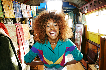 Black woman laughing in retail store on bus