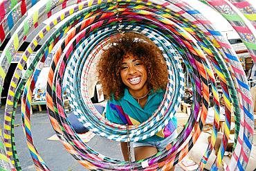 Portrait of smiling black woman behind hoops