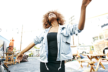 Carefree Black woman dancing outdoors