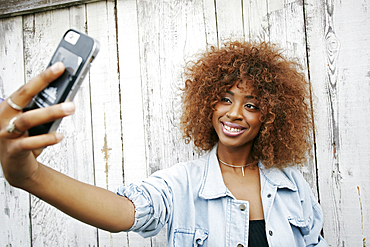Black woman posing for cell phone selfie
