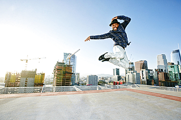 Black man dancing and jumping on urban rooftop