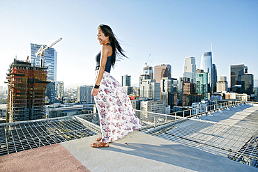 Smiling Asian woman standing on windy urban rooftop