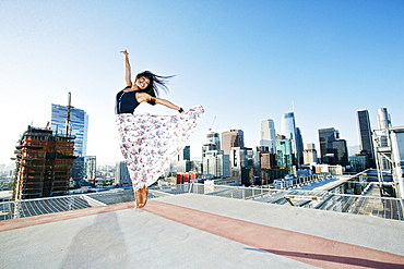 Asian woman jumping on urban rooftop