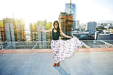 Asian woman dancing on urban rooftop