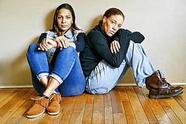 Serious mixed race women sitting on floor
