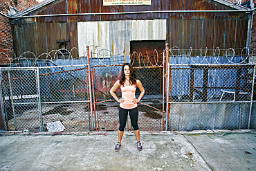 Confident mixed race woman standing on sidewalk near barbed-wire fence