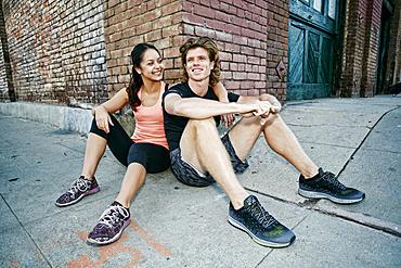 Couple sitting on sidewalk leaning on corner of brick building