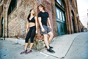 Couple leaning on corner of brick building