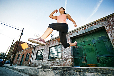 Mixed race woman jumping off loading dock