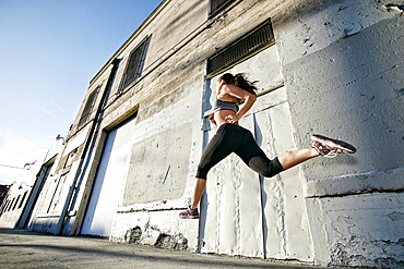 Mixed race woman running and jumping on sidewalk