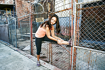 Mixed race woman leaning on chain link fence stretching leg