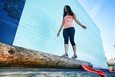 Mixed race woman walking on log