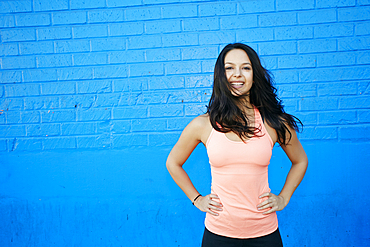 Wind blowing hair of smiling mixed race woman at blue wall