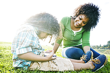 Mixed race mother watching son use cell phone in grass