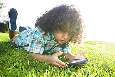 Mixed race boy laying in grass holding cell phone