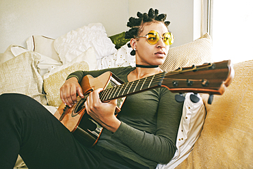 Mixed Race woman sitting on bed playing guitar