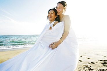 Women wrapped in sheet at beach