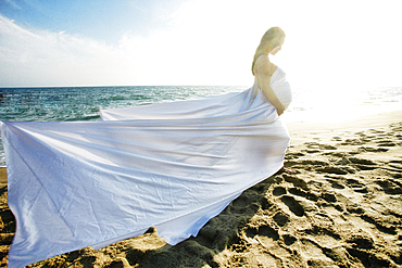 Wind blowing dress of Mixed Race expectant mother at beach