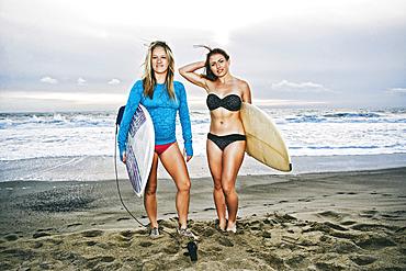 Caucasian women standing on beach holding surfboards