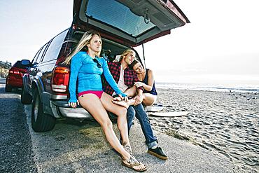 Caucasian friends sitting in car hatch at beach