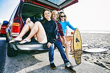 Caucasian friends sitting in car hatch with skateboard
