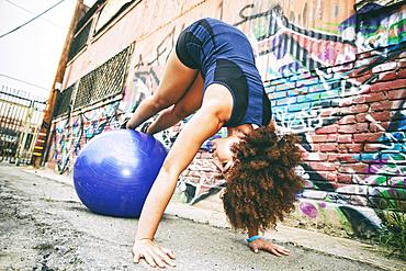 Hispanic woman balancing on fitness ball near graffiti wall