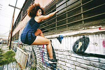 Hispanic woman climbing on bar on graffiti wall