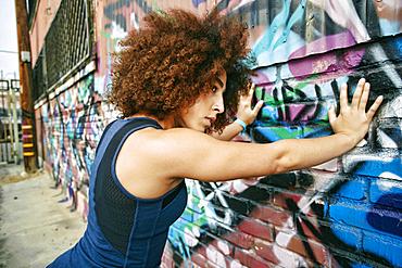 Hispanic woman leaning on graffiti wall
