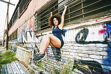 Hispanic woman hanging on bar on graffiti wall