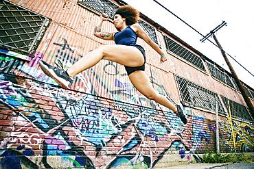Hispanic woman running and jumping near graffiti wall